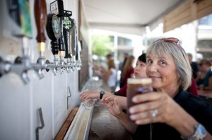 a volunteer pours a pint at one of the beer stations